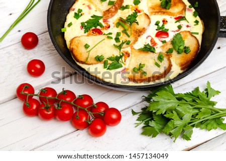 Rustic omelette breakfast with tomatoes and parsley on white rustical background