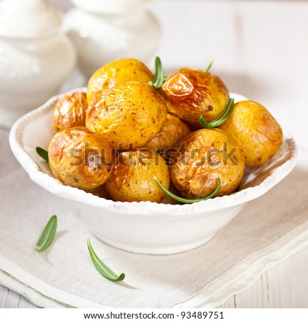 Rustic oven baked potatoes with rosemary - stock photo