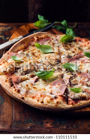 Rustic pizza with ham,  topped with fresh basil