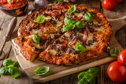Rustic pizza with minced meat cheese, basil on top