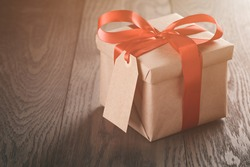 rustic present box with red ribbon on wood table, vintage toned photo