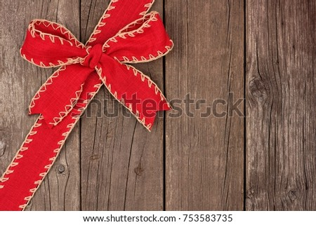 Rustic Red Christmas Bow And Ribbon Diagonal Border Above View On An Old Wood Background