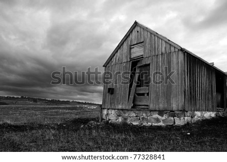 Rustic Ruins Of An Old Abandoned Wooden Shed Decay In A Tasmanian (Australia) Farm Field, While Fierce Rain Clouds Form In The Skies Above