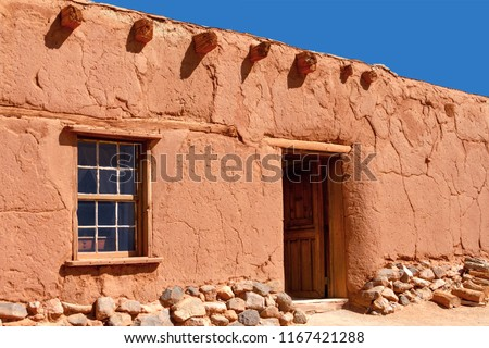 Rustic Santa Fe style adobe duilding with window door