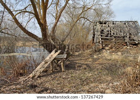 Rustic scenery with old wooden table under tree and ramshackle barn behind
