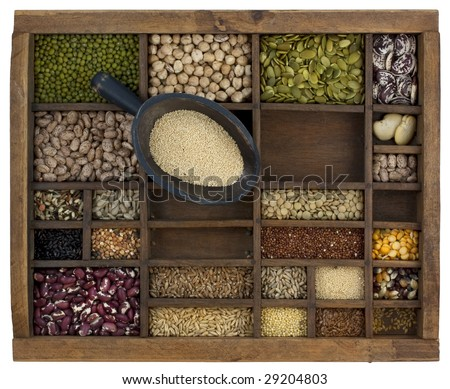 rustic scoop of amaranth grain and a variety of beans, lentils, seeds in old wooden typesetter case, isolated with clipping path
