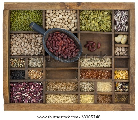 rustic scoop of red kidney beans and a variety of lentils, grain, seeds in old wooden typesetter case, isolated with clipping path
