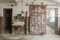 Rustic sliding barn door with decaying sink in an abandoned factory in the deep south