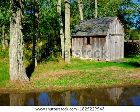 Rustic small barn shed with moss-covered roof in the woods. Water reflections and old trees. stock photo