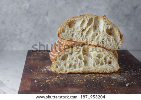 Rustic Sourdough Bread was Cut in Half - Homemade Crunchy Wheat Loaf From Traditional Recipe With Wild Yeast, open crumb, selective focus blurred background. Noise grainy from bread texture