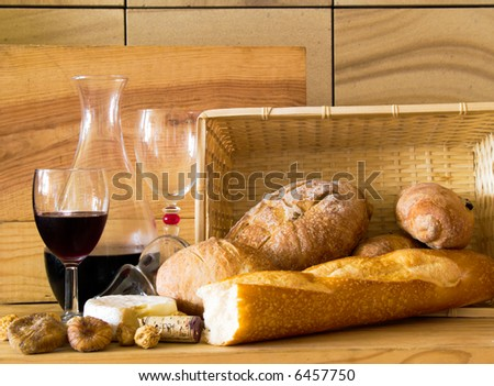 Rustic still life of breads, a cake of Camembert cheese, a decanter of wine, with open stopper, wine glasses and some figs against a wooden board, a wicker basket, and a sandstone wall.