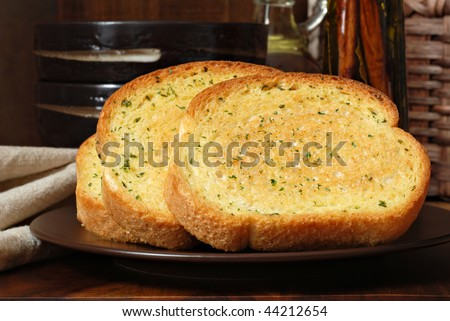 Rustic still life of freshly baked garlic bread seasoned with melted butter and herbs.  Olive oil and stoneware dishes in soft focus in background.