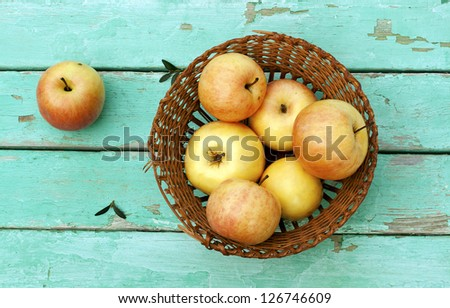 rustic still life with apples on basket on turquoise weathered wood