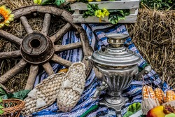 Rustic still life with bast shoes and samovar. Rural landscape with sunflowers, cart wheel, samovar and bast shoes lying on the hay.
