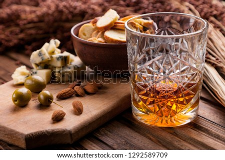 Rustic still life with whiskey and snacks. Crystal glass with a beautiful pattern on a wooden table. Snack for whiskey on crumpled paper olives, crackers, cheese, almonds, pear, apple.