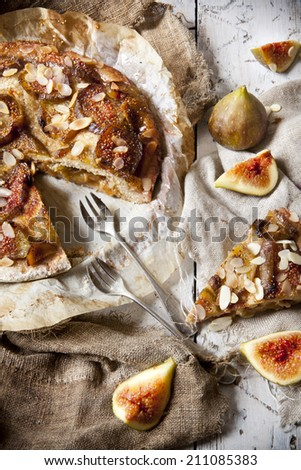 rustic stuffed figs pie covered with almonds and candied figs slices on vintage background with fork fruits and old burlap
