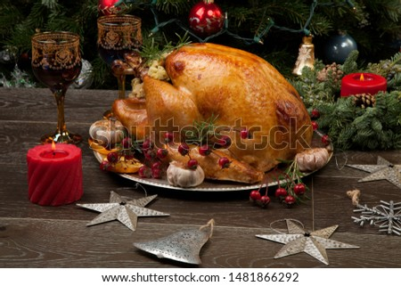 Rustic style roasted Christmas turkey garnished with roasted garlic, lemon, and rosehips. Surrounded with rustic Christmas ornaments, candles, wine, flowers, and Christmas tree in the background.