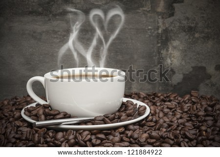 Rustic style setting of hot coffee and coffee beans with heart shape smoke