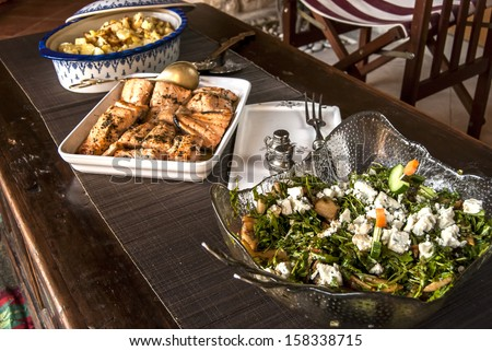 Rustic table with dishes of grilled salmon, salad and sauteed potatoes