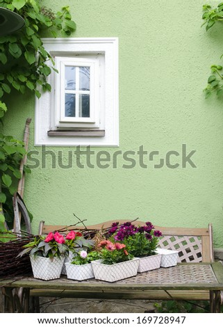 Rustic table with potted flower plants in garden by the green house wall with small white window.