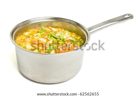 Rustic vegetable and ham broth in stainless steel saucepan isolated on white.