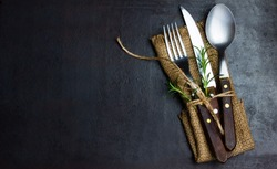 Rustic vintage set of cutlery knife, spoon, fork. Black background. Top view