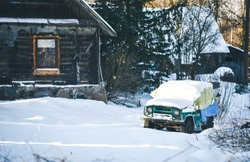 Rustic weathered wood barn and old abandoned car in the snow