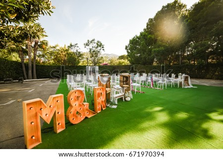 Rustic wedding outdoor photo zone. Hand made wedding decorations includes two big letters M and R, wooden boxes, flowers and plate Love Is In The Air. Weddeing ceremony setup on background.