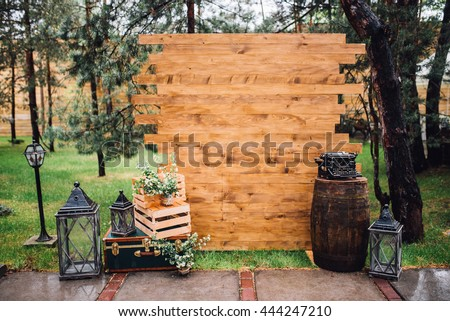 Rustic wedding photo zone. Hand made wedding decorations includes Photo Booth, wooden barrels and boxes, lanterns, suitcases and white flowers and vintage typewriter standing on stump. Horizontal shot