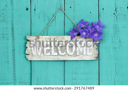 Rustic welcome sign with purple balloon flowers hanging on antique teal blue wooden background