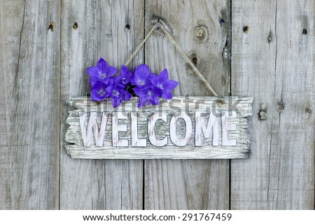 Rustic welcome sign with purple balloon flowers hanging on weathered wooden background
