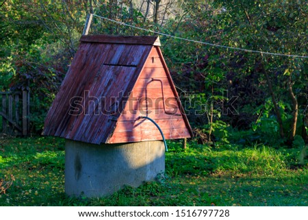 Rustic well on a green lawn in the sun