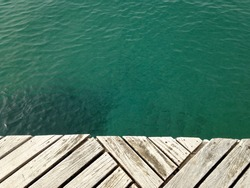 Rustic white decking over turquoise sea, contrasting background