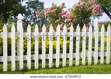 Rustic white picket fence with roses and other flowers in the background. #47064853