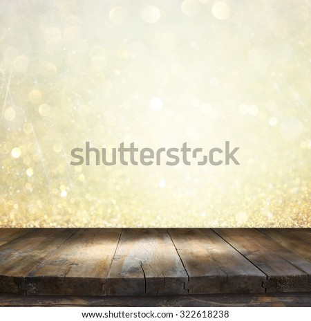 rustic wood table in front of glitter gold and white bright bokeh lights