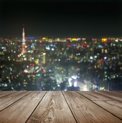 Rustic wood table with blurred city with sky tower and night lights background