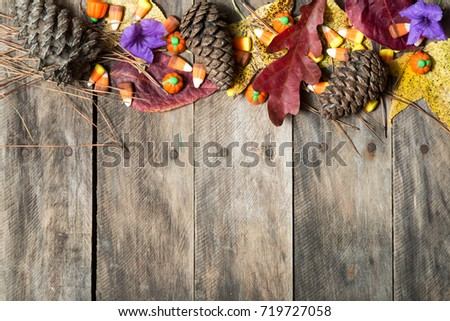rustic wood table with fall decor leaves red yellow orange Halloween candy corn pine cones  #719727058