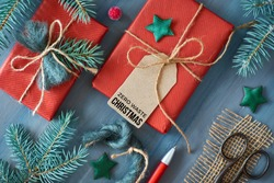 Rustic wooden background with fir branches and Christmas presents gift wrapped in red paper. Ideas for eco friendly decorations. Flat lay, top view, text