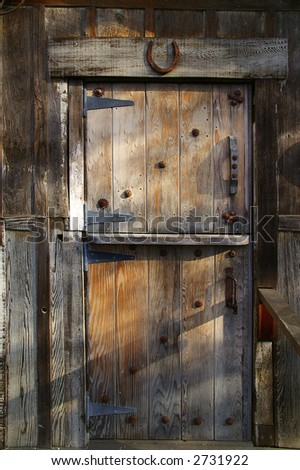 Rustic wooden barn door with rusty metal handles and horseshoe