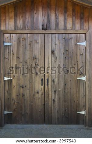 Rustic wooden barn door with rusty metal handles and horseshoe