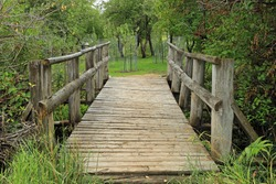 Rustic wooden bridge leading to an orchard, Utah, USA.