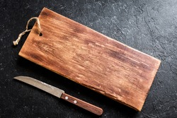 Rustic wooden cutting board and knive on black stone background close up - rustic empty copy space for text, design element