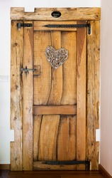 Rustic wooden door with hammered iron reinforcement, heart shaped ornament, private