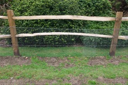 Rustic wooden fence with chicken wire for added protection in front of bush