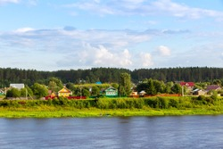 Rustic wooden houses on the bank of the river Sukhona. Old town of Totma, Russia. Rural landscape
