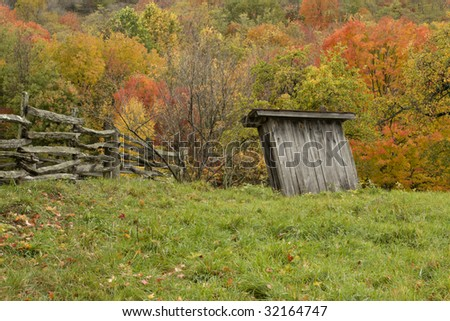 Rustic wooden outhouse  in Virginia Mountains with Fall colors and split rail fence