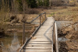 Rustic wooden rickety bridge during early spring floods. Bridge over a flooded stream in Siberia, Russia