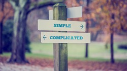 Rustic wooden sign in an autumn park with the words Simple - Complicated offering a choice of action and attitude with arrows pointing in opposite directions in a conceptual image.