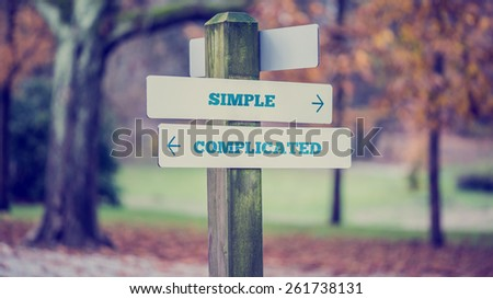 Rustic wooden sign in an autumn park with the words Simple - Complicated offering a choice of action and attitude with arrows pointing in opposite directions in a conceptual image. Foto d'archivio ©
