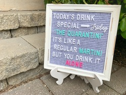 Rustic wooden sign with a daily special spelled out. Inspirational or motivational quote or meme. Felt letter board with multicolored letters on a sidewalk by concrete stairs.